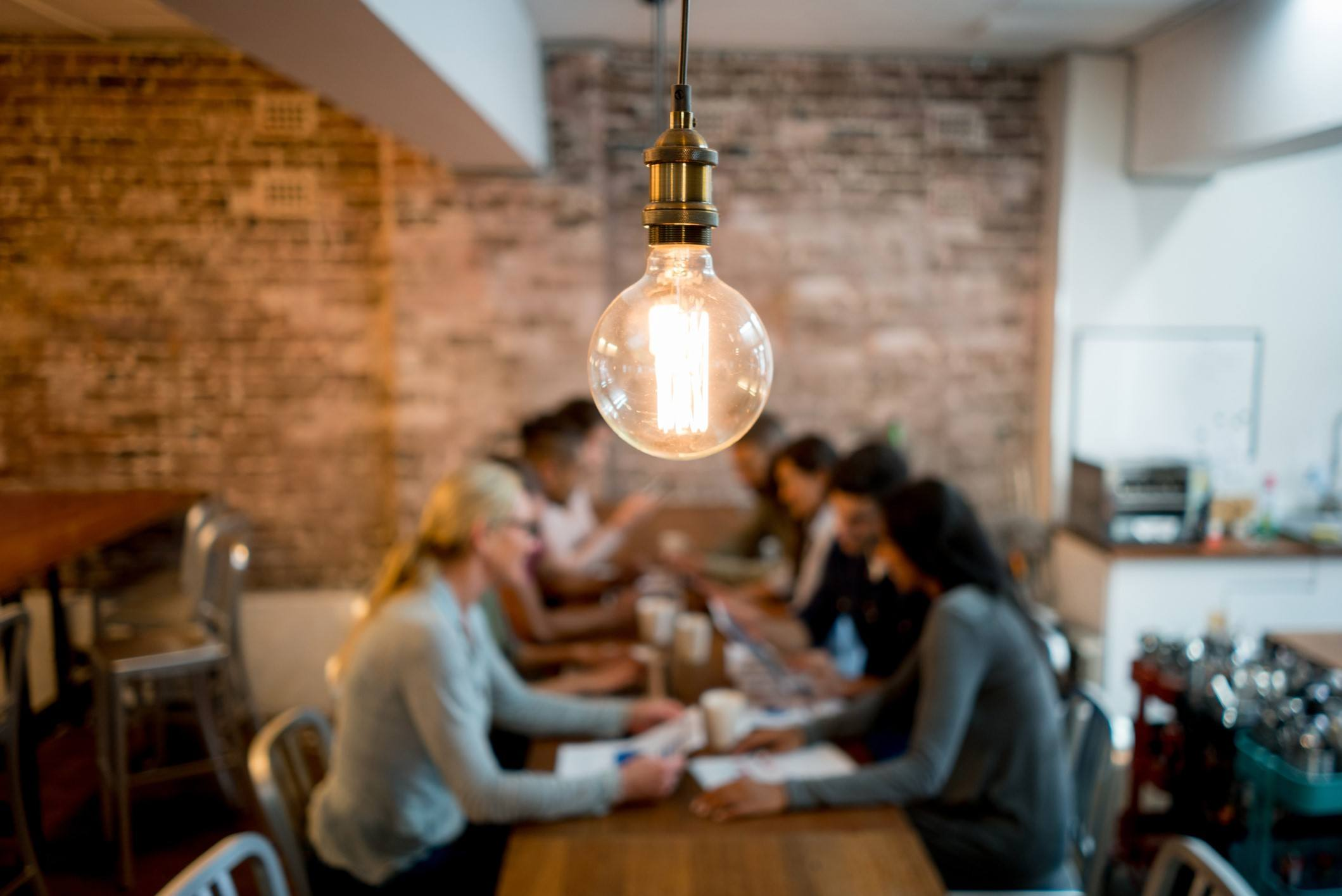 A Light Bulb Above A Table Of People Signifying Good Ideas Happen When We Work Together